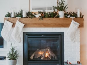 Christmas mantle decor ideas. White brick fireplace with oak mantle is topped with a Crate & Barrel garland. Pottery Barn white stockings are hung from the mantle. White birds are placed in greenery along with a few pillar candles in hurricane glass. A faux tree inside a white pot is placed on the right side and two green pillar candles are mixed in between pot and birds.
