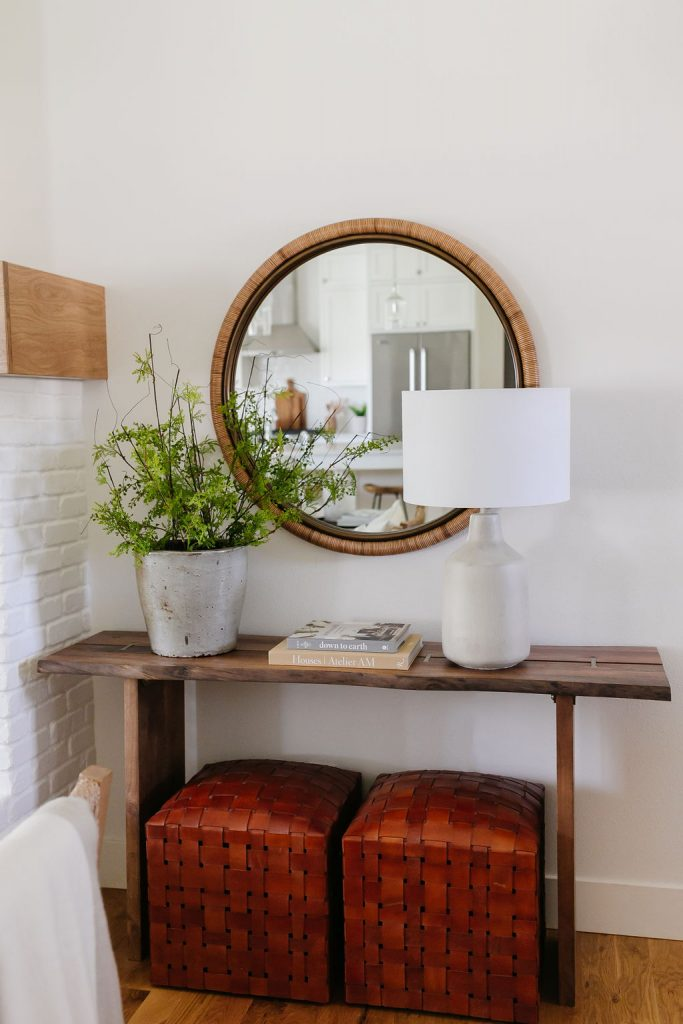Early Black Friday Sales.  World Market console table with McGee & Co leather ottomans styled under it.  Above the console is a Lulu & Georgia large round mirror.  Styled on the console, find two coffee table books, a Lulu & Georgia table lamp and a large pot with faux greenery.