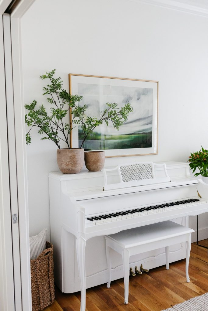 oversized artwork above a piano