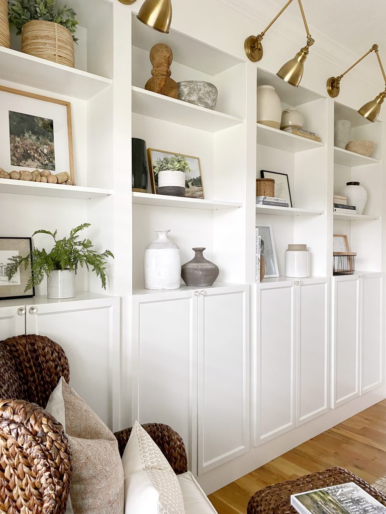 built in shelves styled for spring filled with vases, pots, faux greenery, family photos, artwork