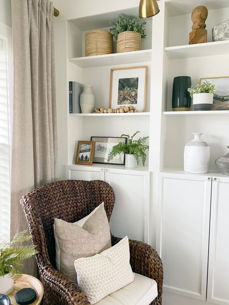 cute reading corner and open shelving filled with faux greenery, objects, artwork, baskets