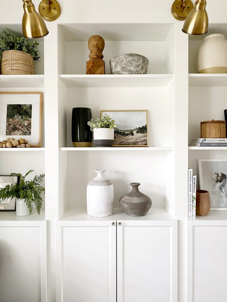 shelves styled for spring with decorative objects, artwork, vases and faux greenery