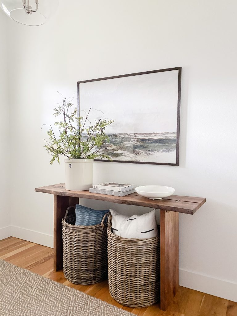 tips for styling your entryway table including artwork above, faux greenery and baskets for storage