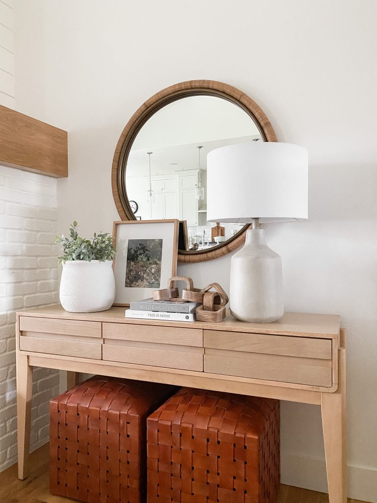 console table with leather ottomans under it for extra seating.  A table lamp, books, decorative objects and a plant are styled on top