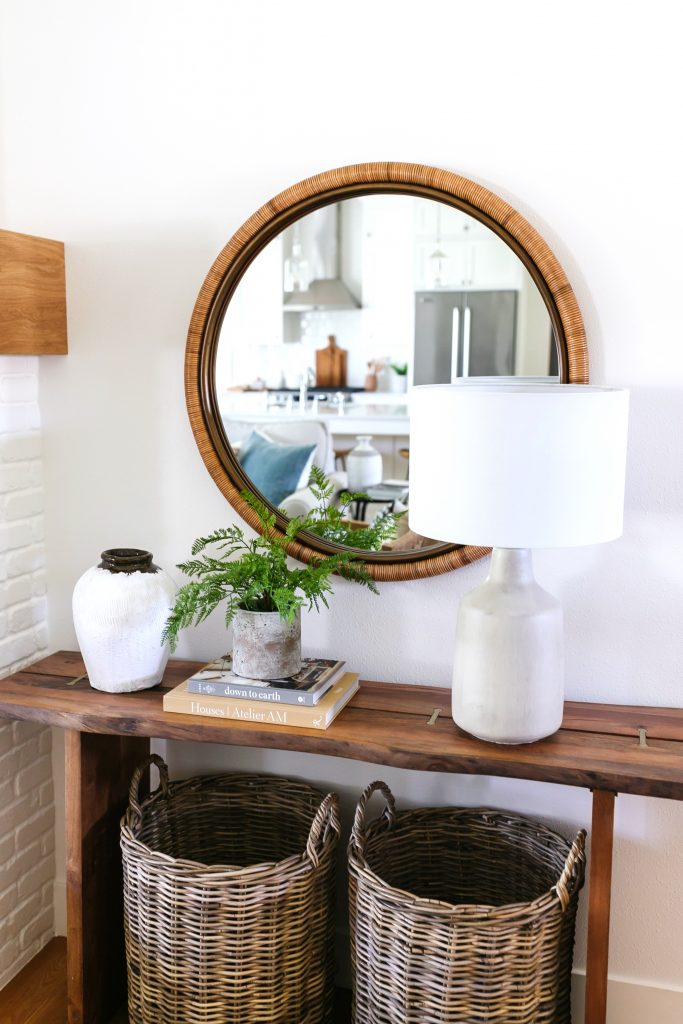 console table styling tips including a round mirror, baskets, table lamp and faux greenery