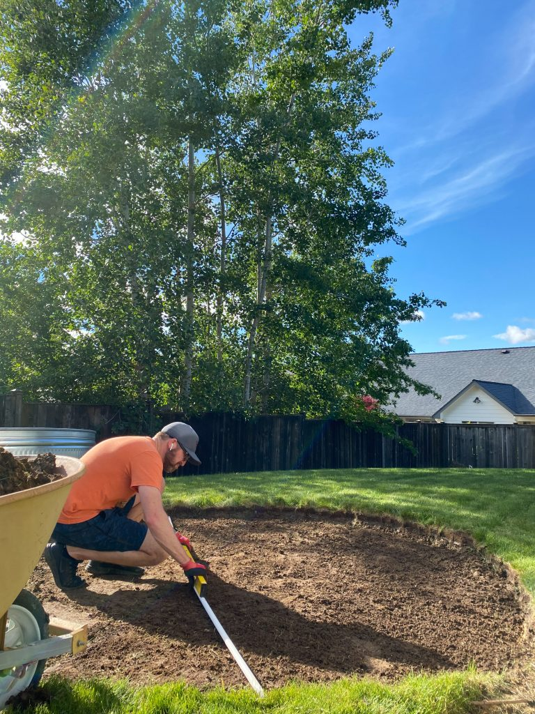 leveling the ground for a backyard stock tank pool.