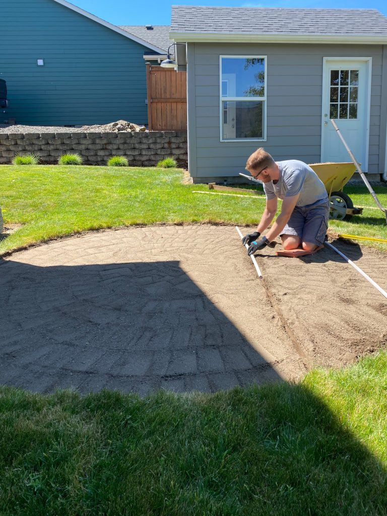 leveling the sand and getting ready to place the backyard stock tank pool