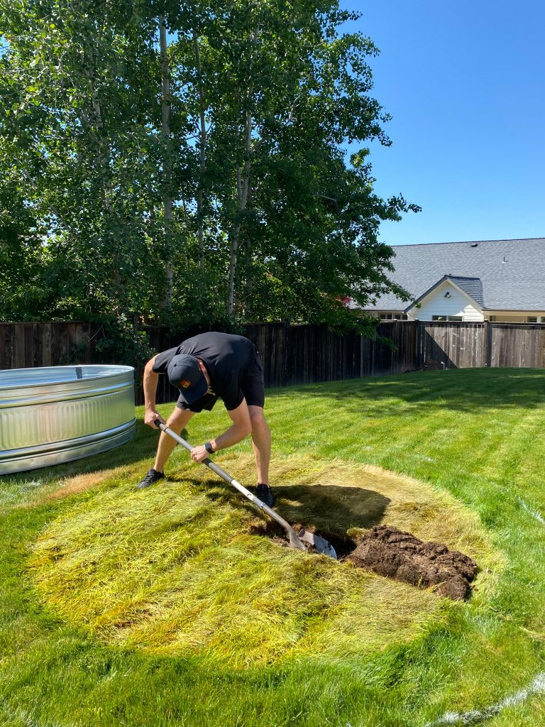 digging out the grass for a backyard stock tank pool