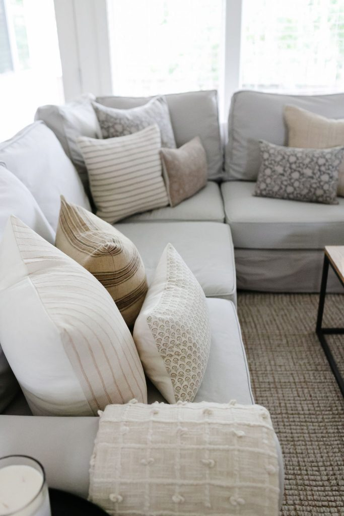 pillows on a sectional are perfect for summer.  Blush striped mixed with a pretty small floral, gray and blush floral pillows mixed with a gray striped pillow