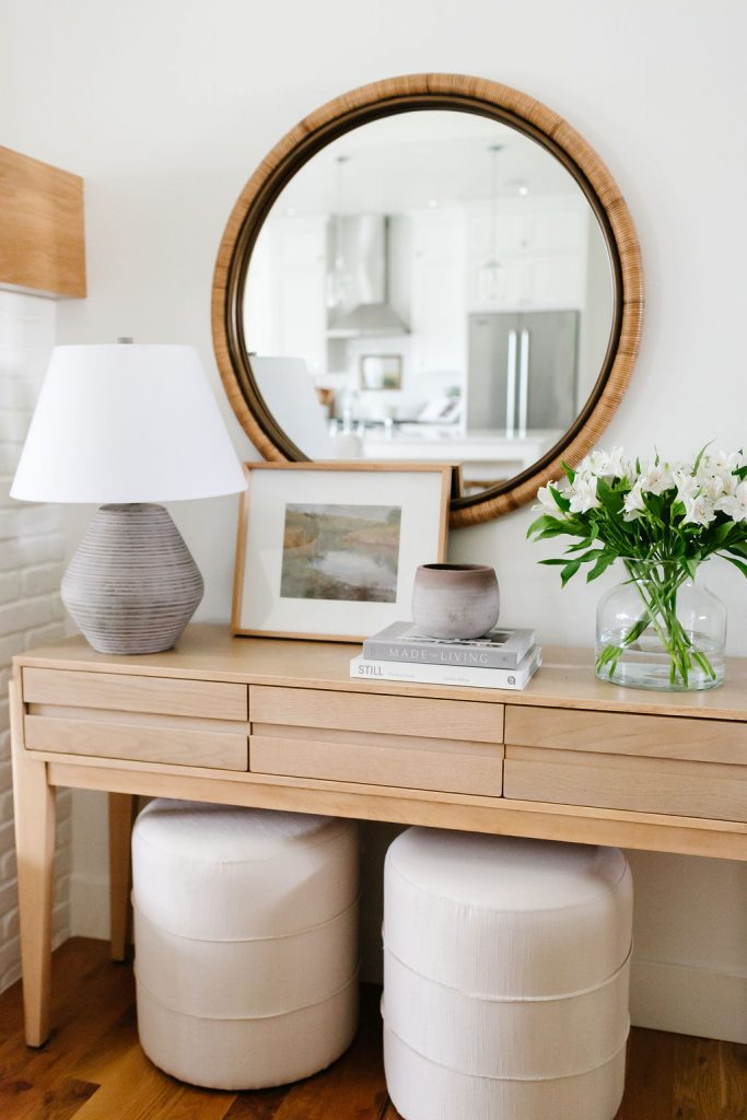 affordable console table decor including a whitewashed pot, coffee table books, glass vase and artwork