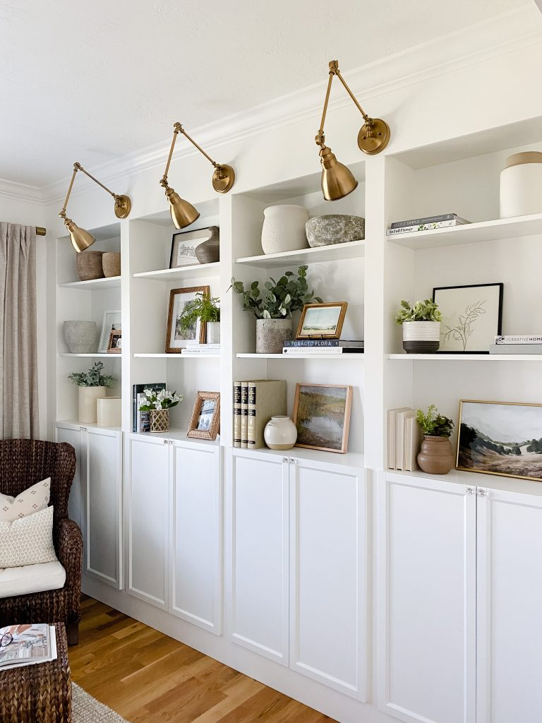 Shelf decor ideas including faux greenery inside pots, fresh flowers inside a vase, pretty summer artwork, books and other decorative objects.
