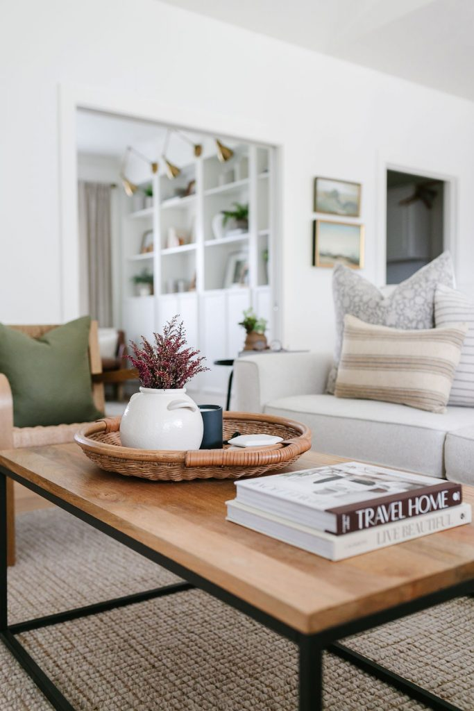 fall living room tour including a basket filled with flowers, a coaster and candle.  Coffee table books
